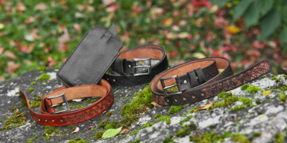 Set of carved leather belts and a phone sleeve