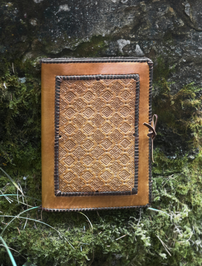 Laced leather notebook covers with hand carved pattern.