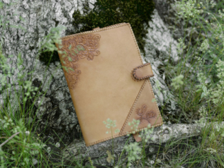 Leather notebook covers with natural finish, decorated by hand carved ornament.