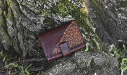 Large leather womens wallet with laced edges and hand carved pattern.