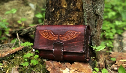 Large leather wallet for women in mahogany with laced edges.