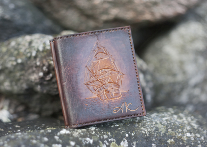 Dark brown leather wallet with a sailing ship image