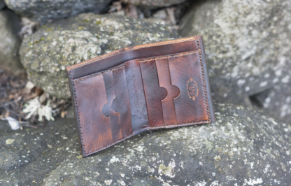 Dark brown leather wallet with a sailing ship image inside