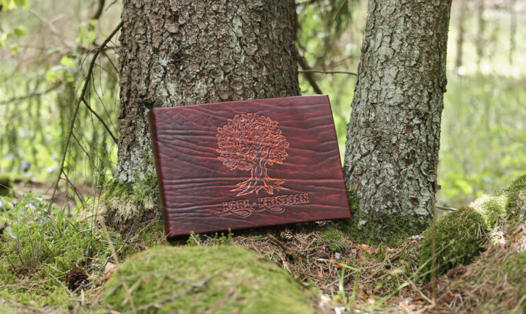 Leather cased photo album with caved oak tree